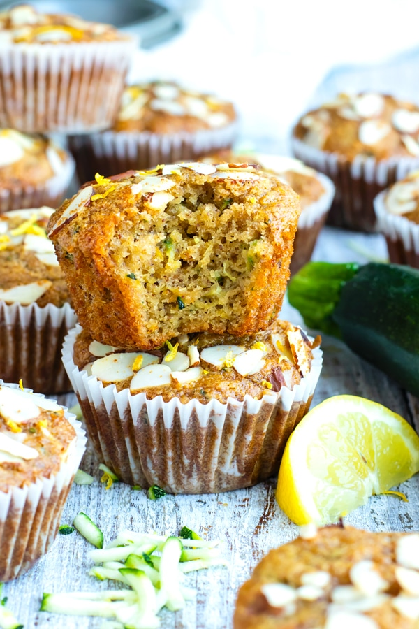 One lemon zucchini muffin with a bite inside on top of another muffin for breakfast.