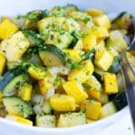 Cooked zucchini and squash with parsley sprinkled on top.