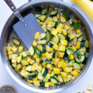 Sautéed zucchini and yellow summer squash in a stainless steel skillet with a spatula.