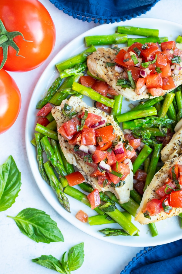A dinner plate serving Whole30 asparagus with seared chicken and a tomato basil bruschetta.