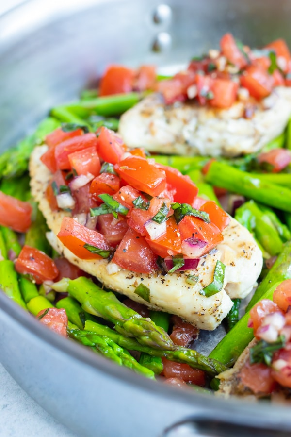 A skillet full of asparagus and a bruschetta chicken recipe with fresh basil and tomatoes.