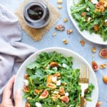 Arugula Fig Salad When fig season is in full swing you can use them up by tossing them into this easy Arugula Fig Salad with a delightful balsamic vinaigrette dressing!  The combination of sweet figs, tart goat cheese, crunchy walnuts, and spicy arugula make all drizzled with a tasty balsamic vinaigrette dressing this one unforgettable and healthy salad recipe!