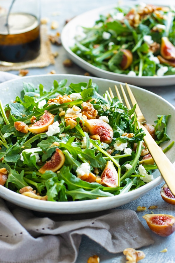 Fig, Goat Cheese Arugula Salad When fig season is in full swing you can use them up by tossing them into this easy Arugula Fig Salad with a delightful balsamic vinaigrette dressing!  The combination of sweet figs, tart goat cheese, crunchy walnuts, and spicy arugula make all drizzled with a tasty balsamic vinaigrette dressing this one unforgettable and healthy salad recipe!