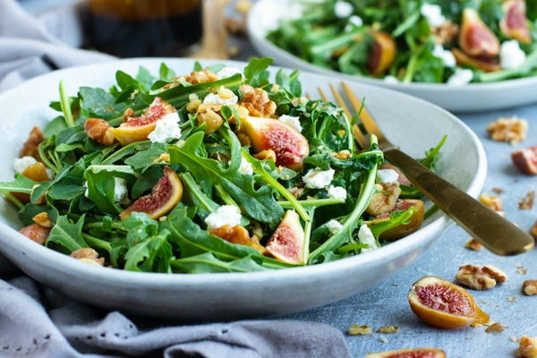 Delicious gluten-free arugula salad in a bowl with a fork.