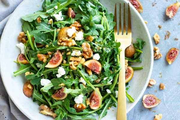 Healthy arugula goat cheese salad in a bowl surrounded by figs.