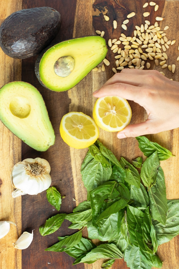 A hand holding a sliced lemon with other ingredients for avocado pesto.