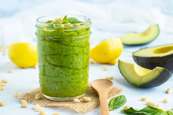 Gluten-free vegan pesto recipe in a glass jar with avocados and lemons on the side.