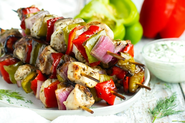 Grilled chicken kabobs in a pile on a white plate.