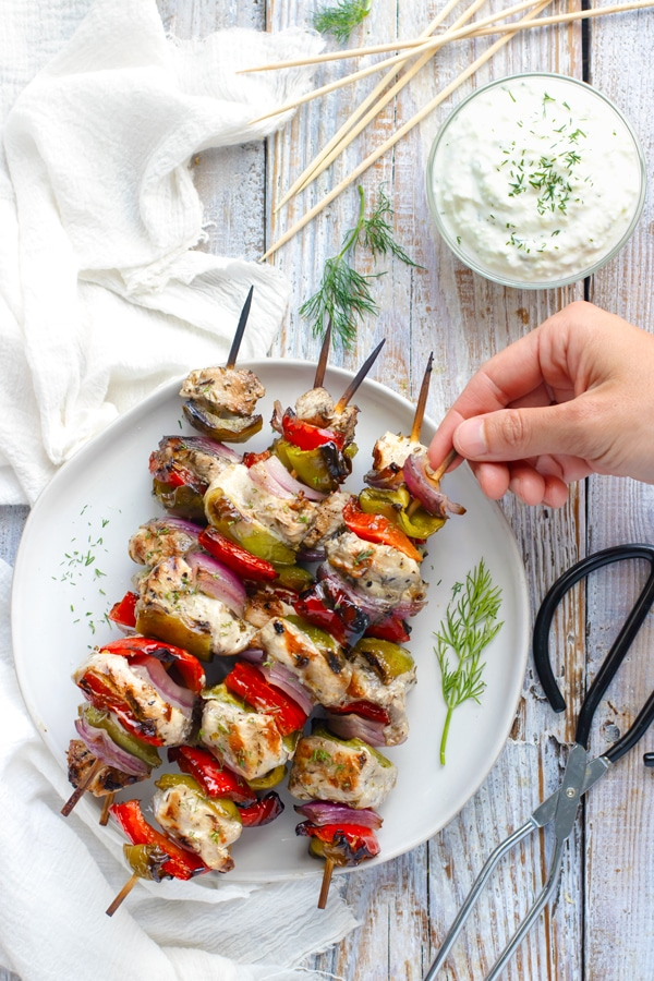 Greek chicken shish-kabob recipe on a white plate.