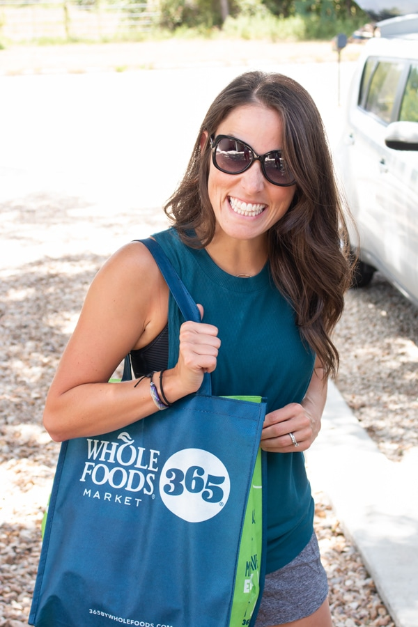 London carrying a Whole Foods shopping bag preparing to make Healthy Taco Salad.