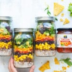 Easy healthy taco salad in mason jars with a jar of salsa on the side.