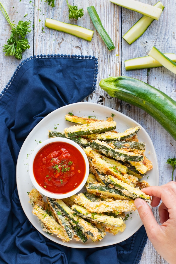 Overhead picture of gluten-free baked zucchini fries on a white plate.