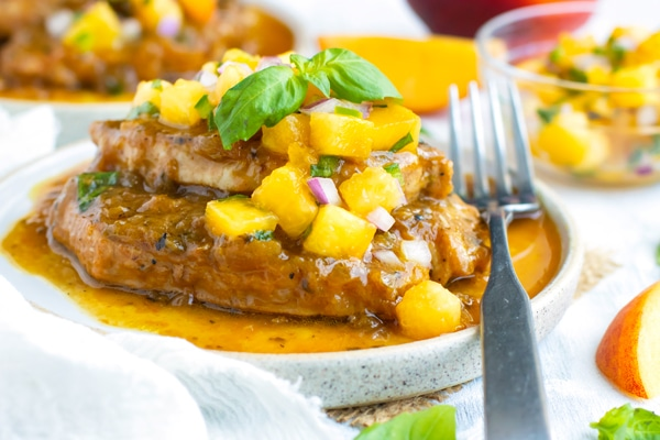 Peach salsa on an Instant Pot pork chop with a fork on the side.