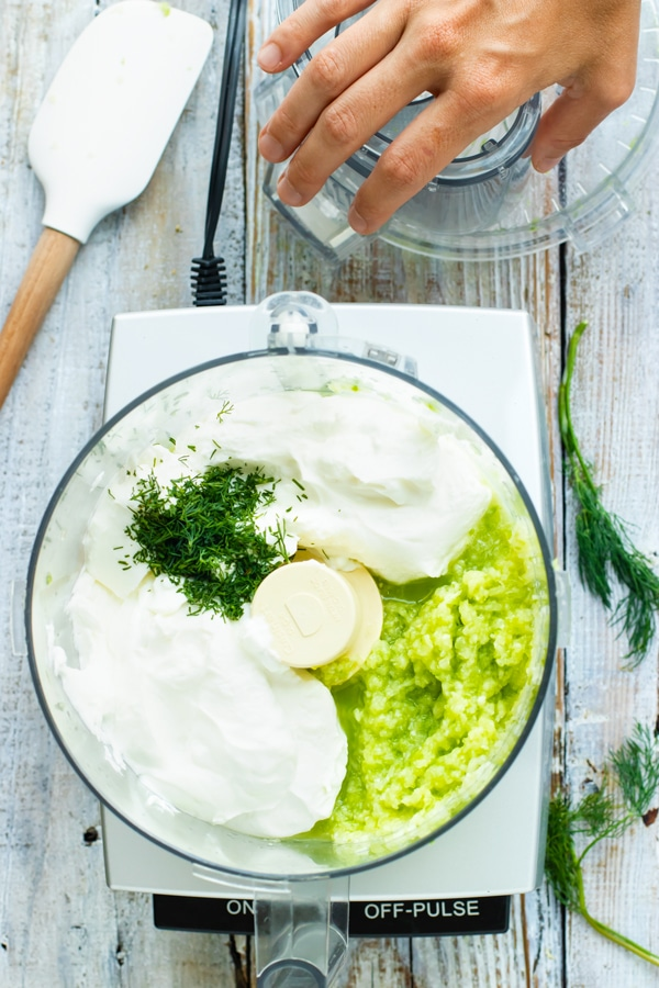 Healthy ingredients for easy tzatziki sauce in a food processor.