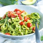Learn how to make Zucchini Noodles with Pesto for a simple, low-carb, dairy-free, vegan, vegetarian, and ketogenic recipe that you can throw together for a healthy workday lunch or busy weeknight!  A vegan pesto recipe is combined with zucchini squash for a light summer dinner!