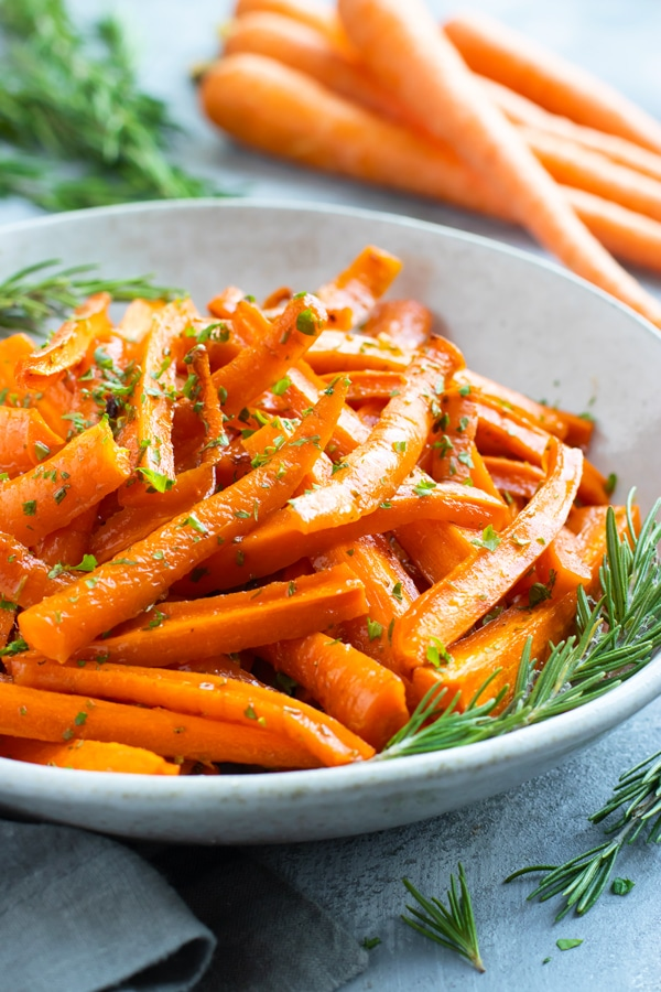 Side picture of roasted carrots in a white bowl with rosemary.