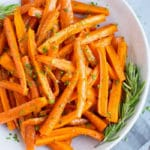 Overhead picture of honey roasted carrots in a white bowl with rosemary.