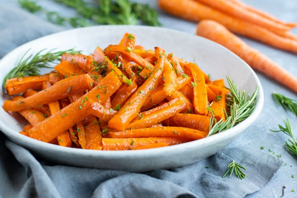 Gluten-free honey roasted carrots in a white bowl with rosemary on the side.