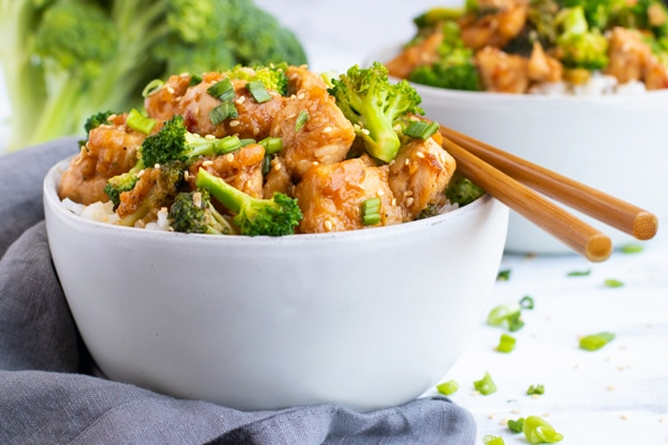Chicken broccoli stir-fry in a white bowl on a white table.