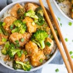 Easy sesame chicken recipe in a white bowl with chopsticks on the side.