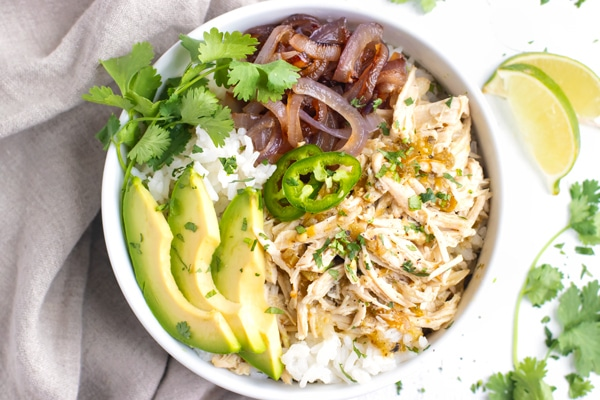 Slow Cooker Shredded Chicken in a white bowl with rice and sliced avocados.