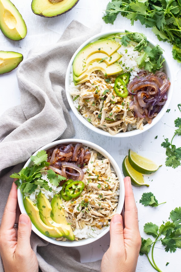Slow cooker shredded chicken recipe in a white bowl with sliced avocado and other ingredients.