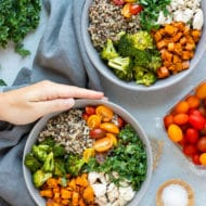 Two hands holding a gray bowl filled with a veggie quinoa bowl recipe.