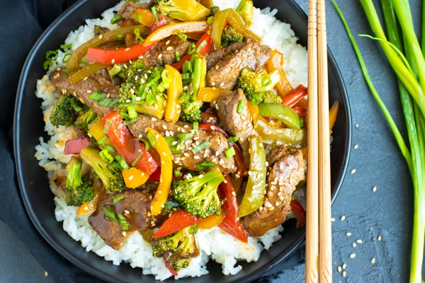 Healthy and easy beef and broccoli stir fry in a black bowl with chopsticks.