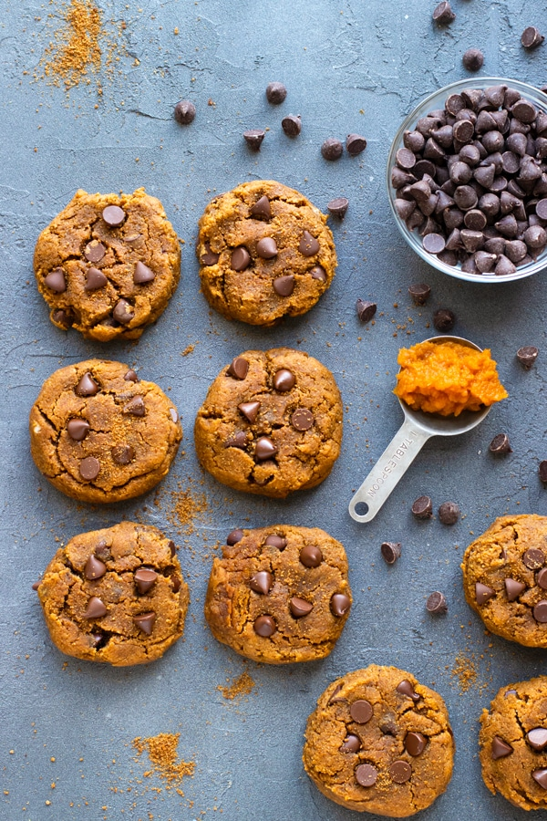 Pumpkin Chocolate Chip Cookies Recipe on a grey backdrop with chocolate chips and pumpkin puree.