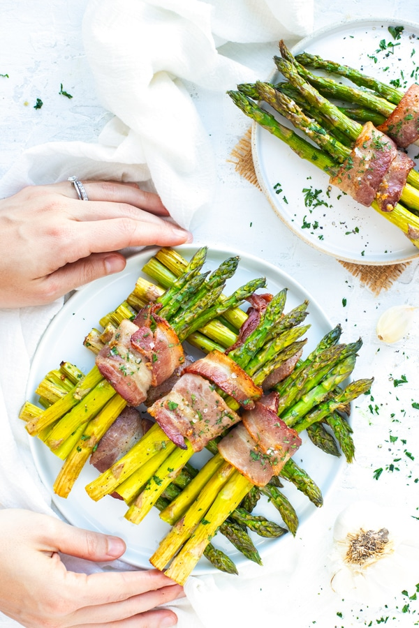 A plate full of bacon wrapped asparagus bundles.