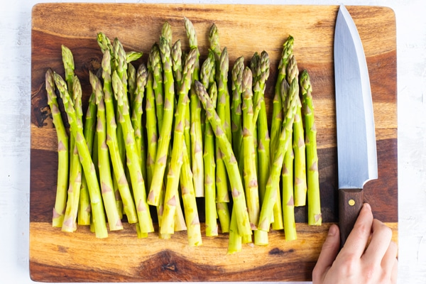 Asparagus stalks on a wooden cutting board as an ingredient in bacon wrapped asparagus recipes.