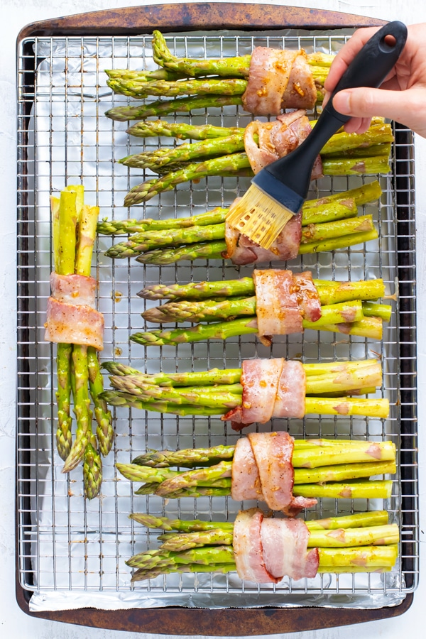Garlic and butter sauce being brushed over bacon wrapped asparagus on a wire rack and baking sheet.