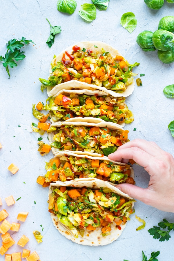 Overhead shot of a hand touching a row of vegan tacos.
