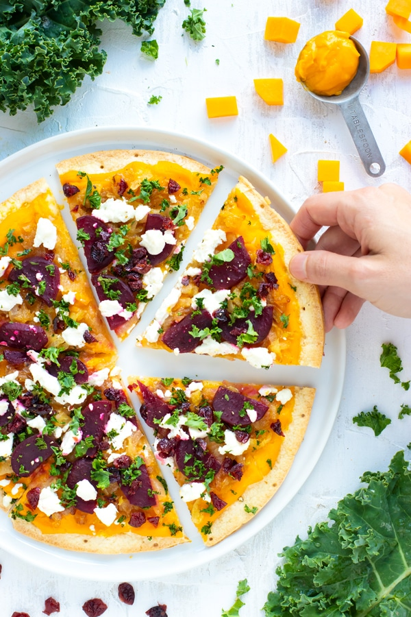 Butternut Squash Pizza is made from a gluten-free pizza crust, covered in a creamy butternut squash pasta sauce, and then topped with beets, caramelized onions, kale, and dried cranberries!  This gluten-free pizza recipe can easily be made vegan and will change up the way you think about your favorite pie!