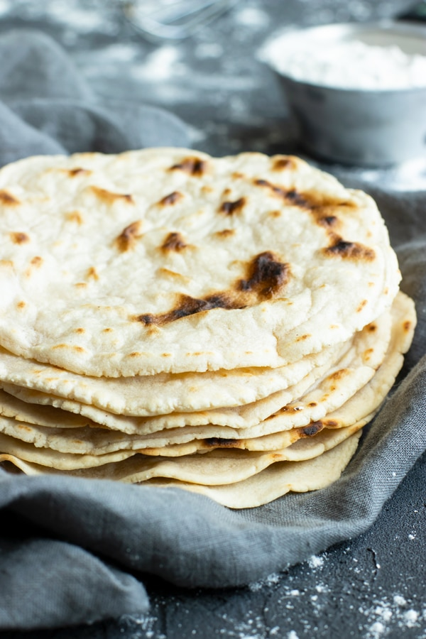 A vertical image of a stack of Paleo Cassava flour tortillas on a gray background.