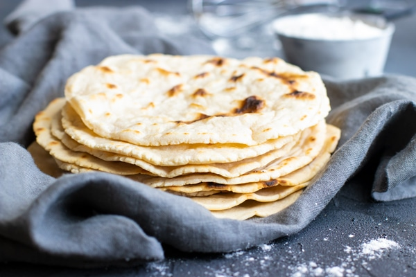 A pile of homemade tortillas with a cup of cassava flour in the background to use on Cassava flour recipes.