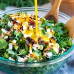 Maple orange vinaigrette being poured over a chopped kale salad recipe in a clear bowl with wooden spoons.