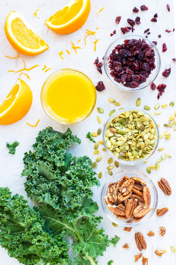 Oranges, cranberries, pumpkin seeds, and pecans in clear bowls with a bunch of kale.