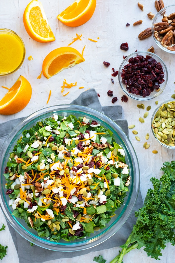 Thanksgiving salad recipe in a clear bowl with oranges, cranberries, and pumpkin seeds surrounding it.