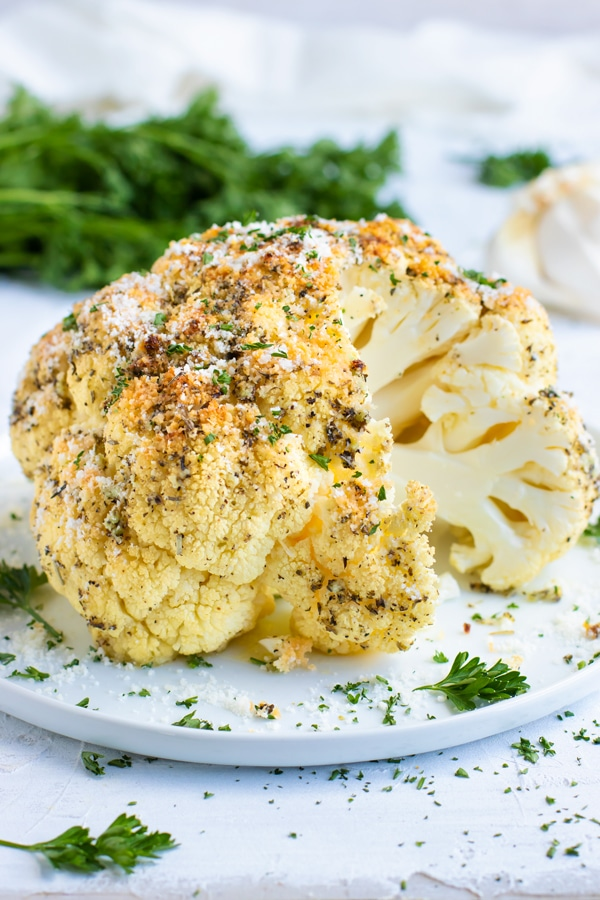 Whole Roasted Cauliflower gets coated in a delicious garlic and herb sauce for an impressive and easy healthy side dish recipe. This oven roasted cauliflower head recipe is gluten-free, dairy-free, vegan, vegetarian, low-carb, keto and Paleo approved!