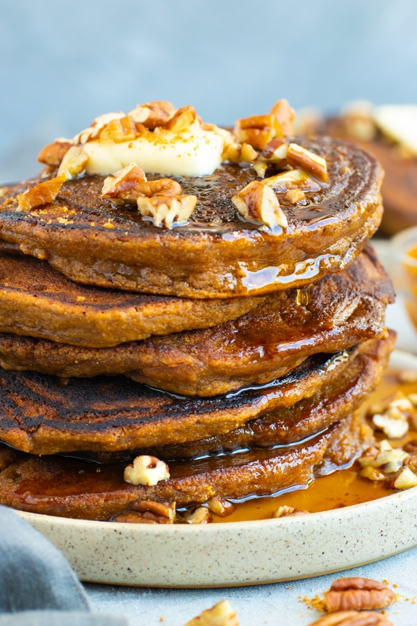 Pumpkin pancakes in a stack with pecans and maple syrup.