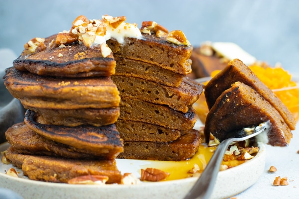 Stack of healthy pumpkin pancakes with a bite taken out.