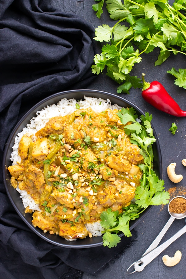 Chicken thighs and korma sauce serve over basmati rice in a black bowl with a black towel, cilantro, and a red pepper.