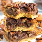 A stack of chocolate pecan pie bars with a bite taken out.