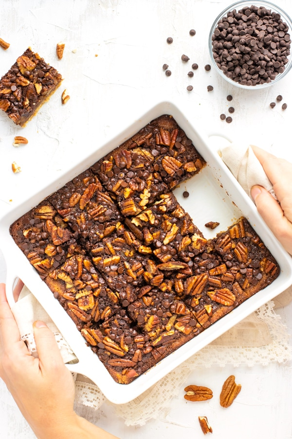 Pecan pie bars in a white baking dish with a bowl of chocolate chips next to it.