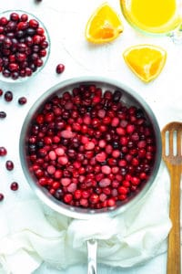Fresh cranberries in a stainless steel skillet with orange slices and a wooden spoon.