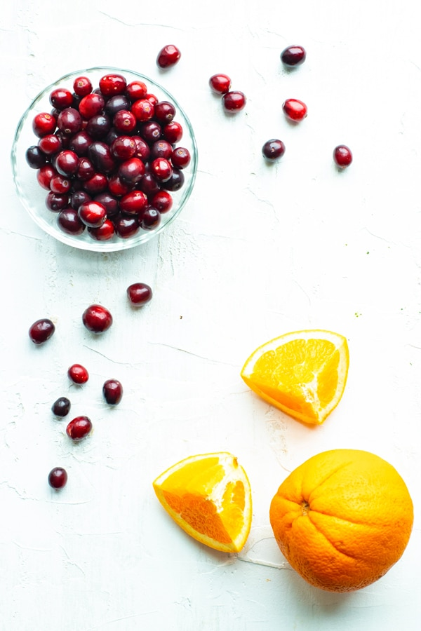Fresh cranberries in a clear bowl and a navel orange with slices next to it.