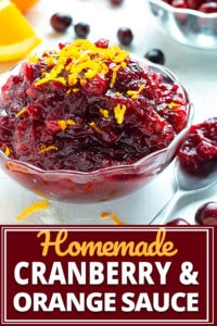 Homemade cranberry sauce in a clear bowl with fresh cranberries on a white background.