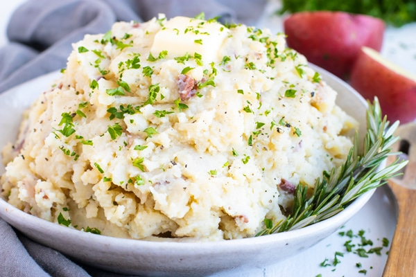 Instant Pot mashed potatoes recipe in a bowl with butter and fresh herbs.