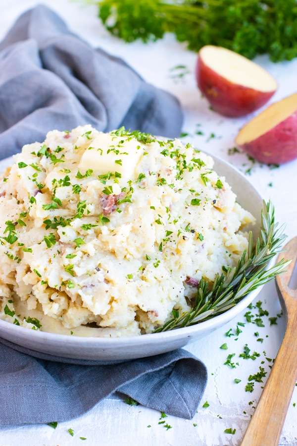 Garlic mashed potatoes in a white bowl with a wooden spoon and red potatoes.